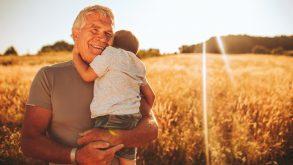 petit-fils dans les bras de son grand-père devant un champ de blé au coucher du soleil