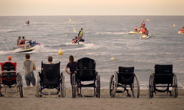 personnes en fauteuil roulant sur la plage, regardant la mer.