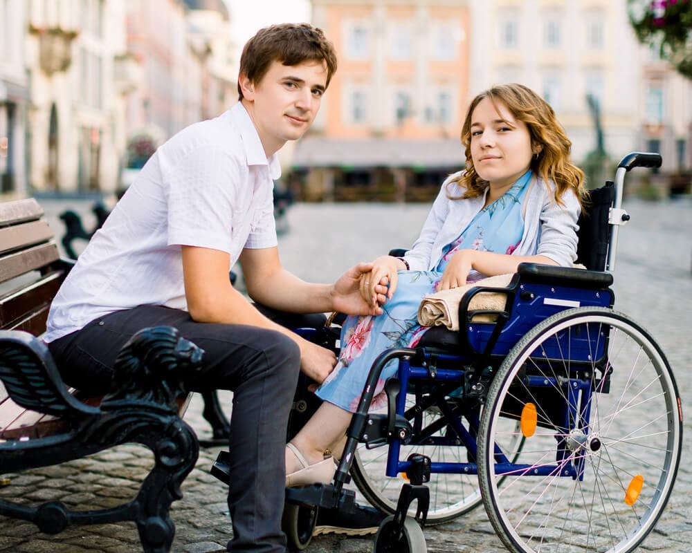 Jeune femme dans un fauteuil roulant en face de son conjoint