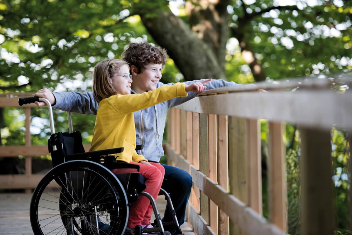 Petite fille en fauteuil roulant montrant quelque-chose à son frère dans le jardin
