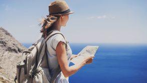 Jeune femme devant la mer regardant une carte