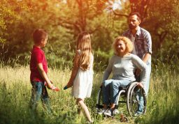 Mère en fauteuil roulant poussé par son mari jouant avec ses enfants