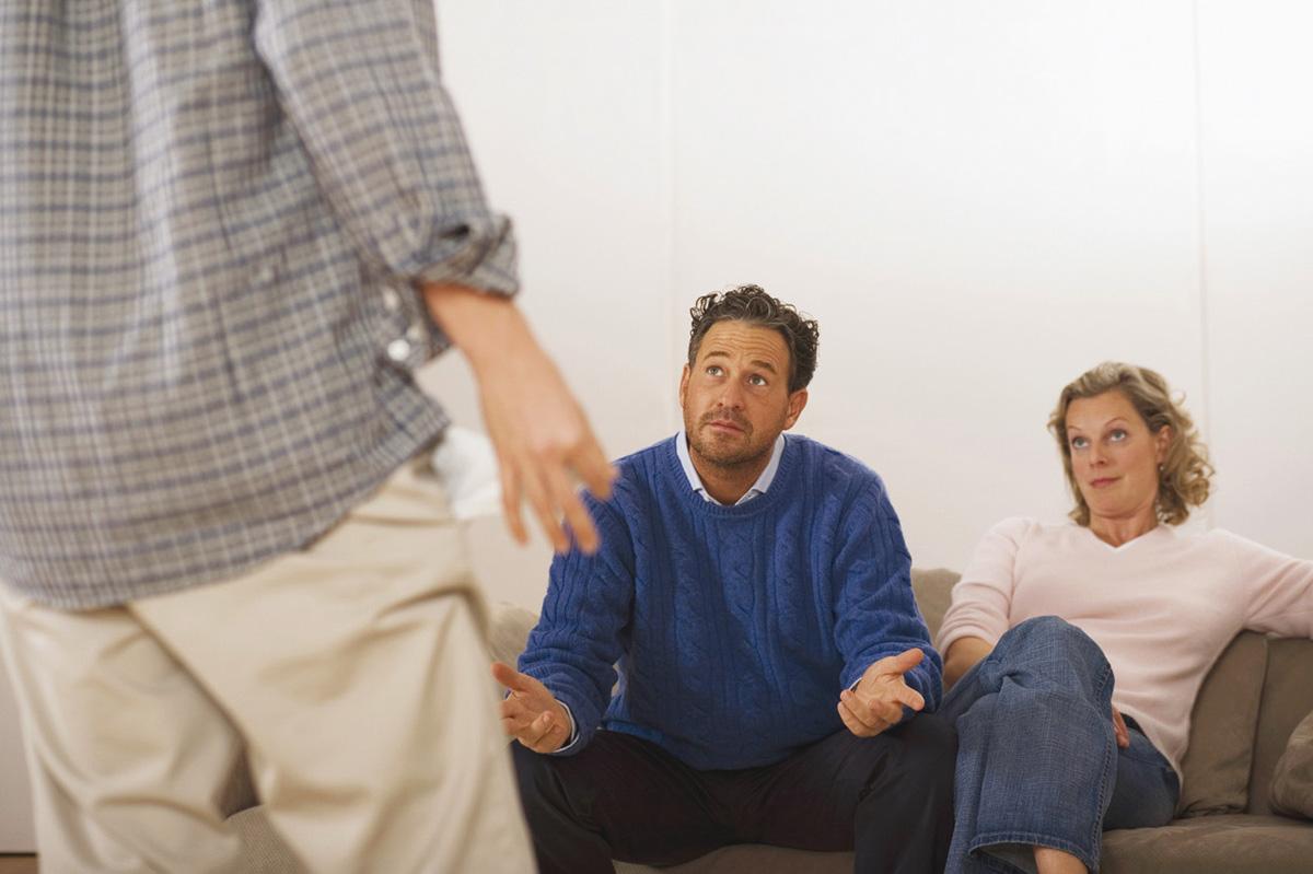 parents assis dans un canapé, en discussion avec leur fils