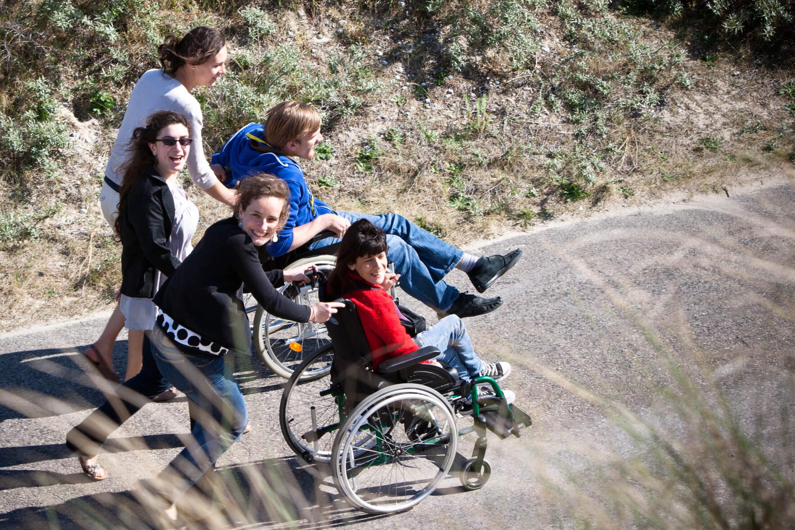 Groupe de jeunes souriants sur la route avec un jeune en fauteuil