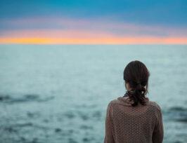 une femme de dos face à la mer