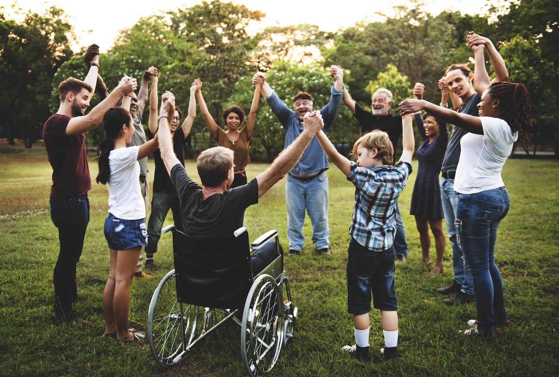 Ronde de personnes se tenant par la main dans un parc