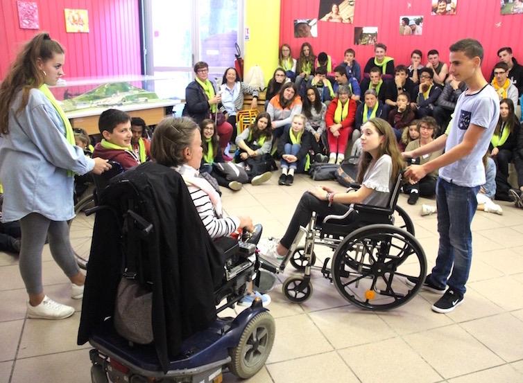 Personne handicapée témoignant devant un groupe de jeunes à Lourdes