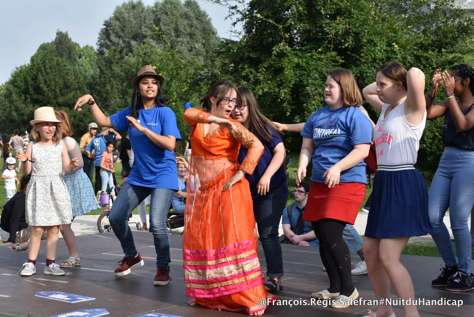 Jeune fille trisomique en train de danser sur scène pour la Nuit du handicap
