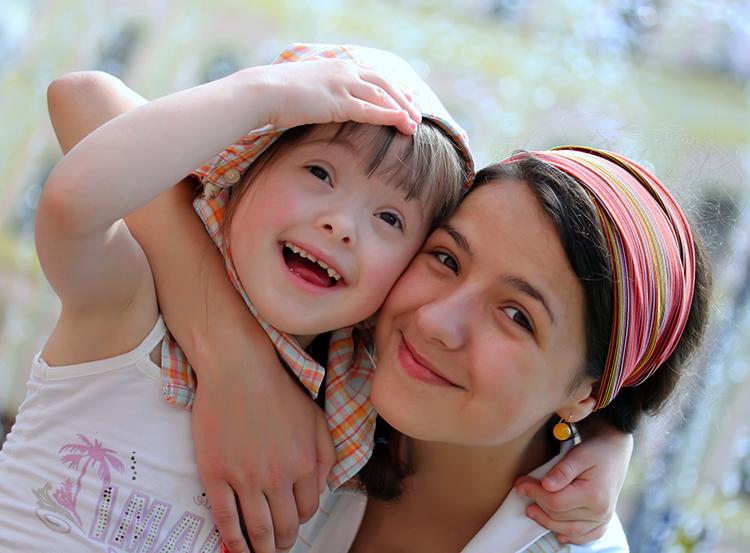 Deux jeunes filles souriantes dont l'une est trisomique