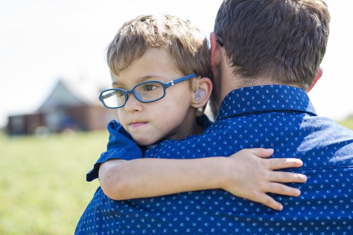 Un papa qui tient dans ses bras son petit garçon sourd