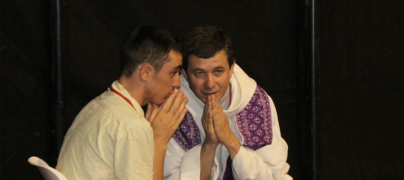 Personne handicapée avec un prêtre pendant le sacrement de réconciliation