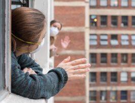 deux personnes se saluant de leur fenêtre.