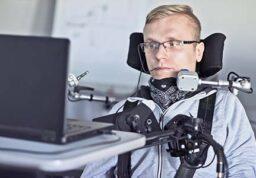 un homme handicapé devant son ordinateur.