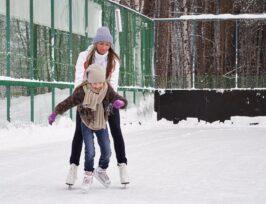 une femme aide une enfant à patiner.