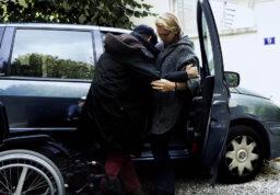 une femme aidant son mari handicapé à l'installer dans leur voiture.