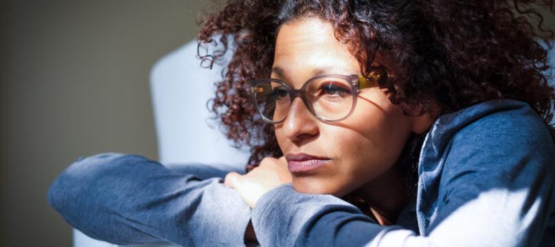 Une femme désemparée en train de réfléchir, accoudée à son canapé