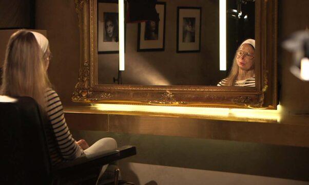 une femme au visage défiguré devant un miroir