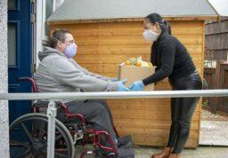 entraide entre une personne en fauteuil roulant et un adulte.