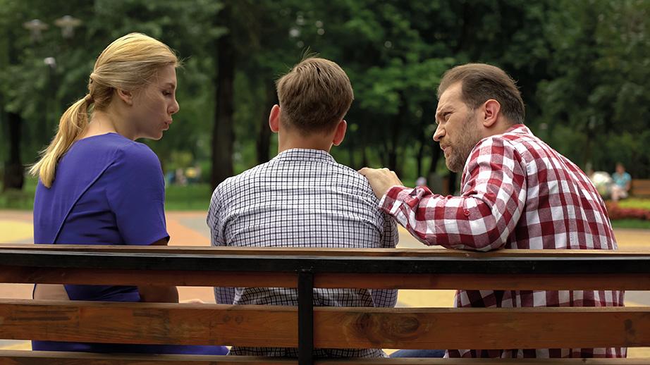 Deux parents sur un banc avec leur adolescent, vus de dos