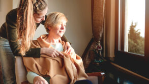 Une jeune femme entoure de soins une femme plus âgée