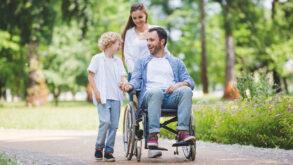 Un jeune garçon à côté de son père en fauteuil roulant