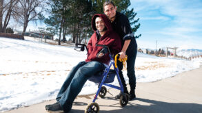 Deux jeunes hommes souriants dont l'un est handicapé