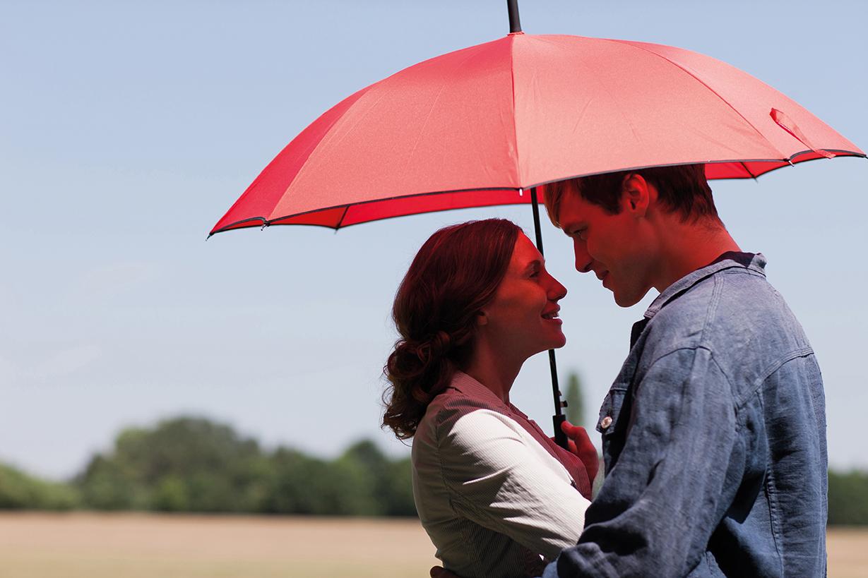 Un couple de profil sous un parapluie rouge