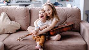 Une fillette et son petit frère handicapé assis dans un canapé