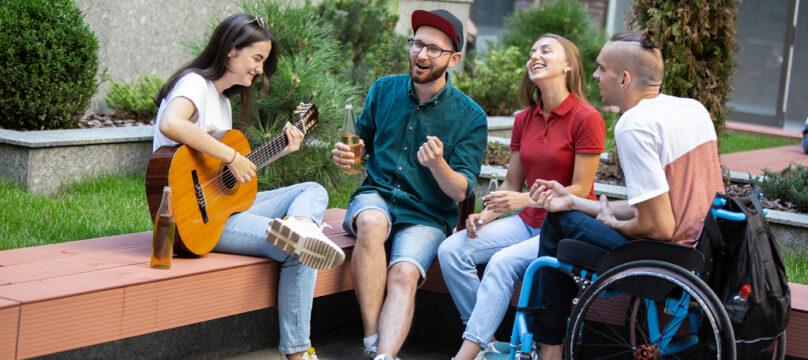 Un groupe de jeunes l'été dont l'un est atteint d'un handicap
