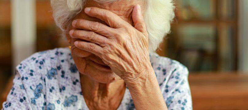 Personne âgée qui a l'air triste. Elle a la tête dans ses mains.