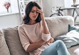 une femme, fatiguée, assise sur son canapé