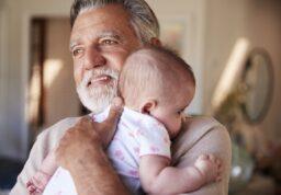 Un grand-père tient son petit-enfant dans les bras.